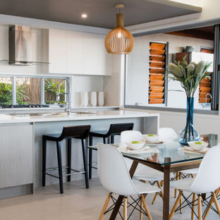 This is an example of a contemporary l-shaped kitchen in Brisbane with flat-panel cabinets, white cabinets, window splashback, with island, grey floor and white benchtop.