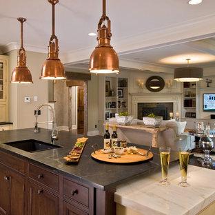 Свежая идея для дизайна: кухня-гостиная в классическом стиле с техникой из нержавеющей стали, столешницей из талькохлорита, врезной раковиной, фасадами с декоративным кантом и темными деревянными фасадами - отличное фото интерьера