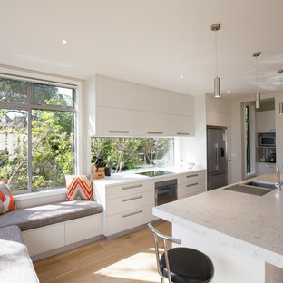 Large eat-in kitchen ideas - Inspiration for a large galley light wood floor eat-in kitchen remodel in Auckland with an undermount sink, flat-panel cabinets, white cabinets, quartz countertops, glass sheet backsplash, stainless steel appliances and an island