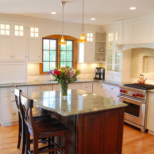 Eat-in kitchen - mid-sized traditional u-shaped light wood floor eat-in kitchen idea in Chicago with flat-panel cabinets, white cabinets, green backsplash, subway tile backsplash, stainless steel appliances, an undermount sink, granite countertops and an island