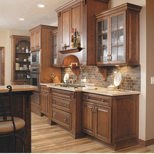 Open concept kitchen - large traditional galley light wood floor open concept kitchen idea in Other with an undermount sink, glass-front cabinets, medium tone wood cabinets, quartz countertops, multicolored backsplash, stone tile backsplash, stainless steel appliances and a peninsula