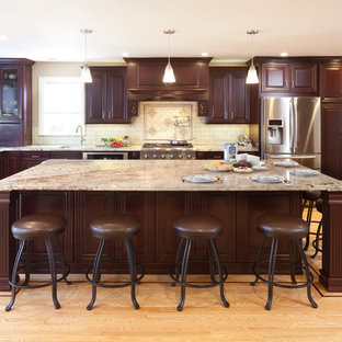 Photo of a large traditional l-shaped kitchen in San Francisco with raised-panel cabinets, dark wood cabinets, beige splashback, stainless steel appliances, a submerged sink, granite worktops, medium hardwood flooring, an island and travertine splashback.