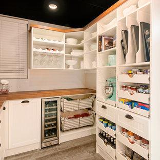 Mittelgroße Landhaus Küche mit Vorratsschrank, offenen Schränken, weißen Schränken, Arbeitsplatte aus Holz, Porzellan-Bodenfliesen, braunem Boden und brauner Arbeitsplatte in Sonstige