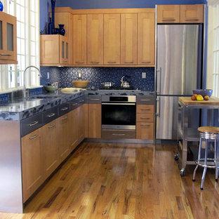 Новый формат декора квартиры: отдельная, угловая кухня среднего размера в стиле фьюжн с врезной раковиной, фасадами в стиле шейкер, светлыми деревянными фасадами, синим фартуком, фартуком из стеклянной плитки, техникой из нержавеющей стали, светлым паркетным полом и синей столешницей