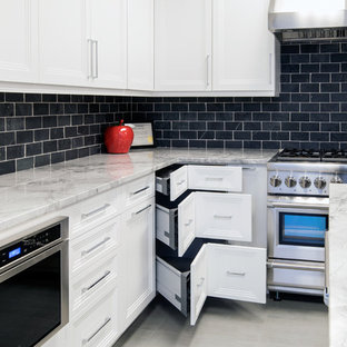 Inspiration for a mid-sized transitional l-shaped eat-in kitchen in Other with an undermount sink, recessed-panel cabinets, white cabinets, quartzite benchtops, black splashback, slate splashback, stainless steel appliances, porcelain floors, with island, grey floor and grey benchtop.
