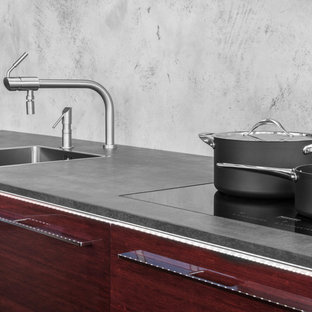 Inspiration for a medium sized contemporary galley kitchen/diner in Other with a built-in sink, flat-panel cabinets, red cabinets, granite worktops, grey splashback, black appliances, plywood flooring and an island.
