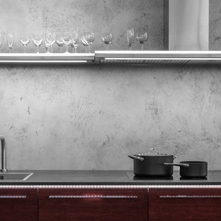 Photo of a medium sized contemporary galley kitchen/diner in Other with a built-in sink, flat-panel cabinets, red cabinets, granite worktops, grey splashback, black appliances, plywood flooring and an island.