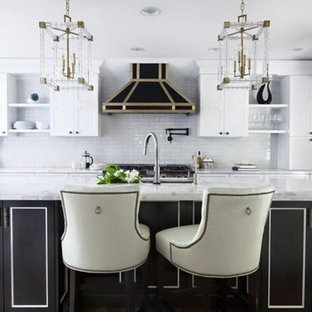 Photo of a mid-sized contemporary eat-in kitchen in Los Angeles with an undermount sink, recessed-panel cabinets, grey cabinets, marble benchtops, white splashback, ceramic splashback, black appliances, medium hardwood floors and with island.