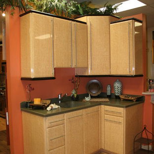 This is an example of a small asian l-shaped eat-in kitchen in Miami with an undermount sink, raised-panel cabinets, beige cabinets, solid surface benchtops, orange splashback, stainless steel appliances, laminate floors and no island.