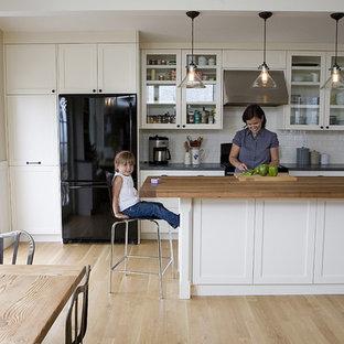 Ejemplo de cocina comedor en L, clásica, con armarios tipo vitrina, encimera de madera, puertas de armario blancas, salpicadero blanco, salpicadero de azulejos tipo metro y electrodomésticos negros