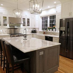 Große Klassische Küche in L-Form mit Landhausspüle, Kassettenfronten, weißen Schränken, Quarzwerkstein-Arbeitsplatte, Küchenrückwand in Grau, Rückwand aus Travertin, Küchengeräten aus Edelstahl, braunem Holzboden, zwei Kücheninseln, gelbem Boden und weißer Arbeitsplatte in Boston
