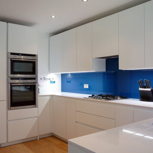 Inspiration for a medium sized modern u-shaped kitchen/diner in London with a submerged sink, flat-panel cabinets, white cabinets, engineered stone countertops, blue splashback, glass sheet splashback, stainless steel appliances, light hardwood flooring and no island.