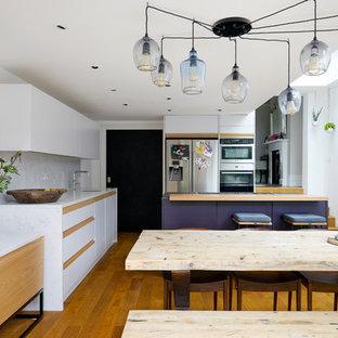 ロンドンの大きいコンテンポラリースタイルのおしゃれなキッチン (一体型シンク、フラットパネル扉のキャビネット、紫のキャビネット、人工大理石カウンター、白いキッチンパネル、石スラブのキッチンパネル、シルバーの調理設備の、無垢フローリング、茶色い床) の写真