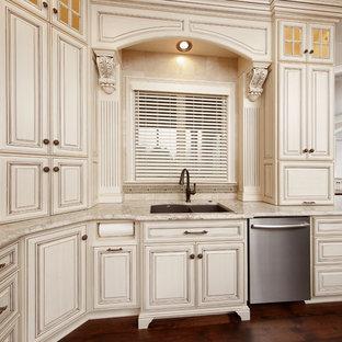 Geschlossene, Mittelgroße Klassische Küche in U-Form mit Unterbauwaschbecken, profilierten Schrankfronten, weißen Schränken, Granit-Arbeitsplatte, Küchenrückwand in Beige, Rückwand aus Travertin, Küchengeräten aus Edelstahl, dunklem Holzboden und braunem Boden in Sonstige