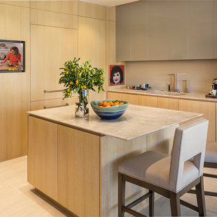 Small contemporary u-shaped kitchen in Los Angeles with an integrated sink, flat-panel cabinets, light wood cabinets, quartzite benchtops, beige splashback, glass sheet splashback, panelled appliances, porcelain floors and with island.