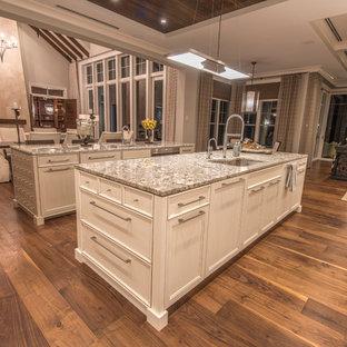 Foto på ett stort tropiskt kök, med en undermonterad diskho, skåp i shakerstil, vita skåp, granitbänkskiva, grått stänkskydd, stänkskydd i glaskakel, integrerade vitvaror, ljust trägolv och flera köksöar