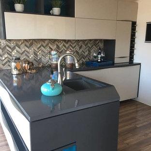 オーランドの小さいモダンスタイルのおしゃれなキッチン (レイズドパネル扉のキャビネット、ベージュのキャビネット、珪岩カウンター、マルチカラーのキッチンパネル、モザイクタイルのキッチンパネル、濃色無垢フローリング、茶色い床、緑のキッチンカウンター) の写真