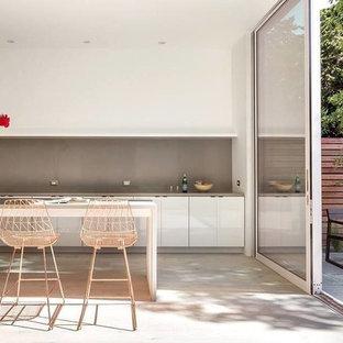 Idéer för ett mellanstort asiatiskt beige linjärt kök och matrum, med en nedsänkt diskho, släta luckor, vita skåp, bänkskiva i kvartsit, beige stänkskydd, stänkskydd i mosaik, vita vitvaror, cementgolv, en köksö och vitt golv