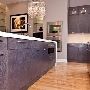 Inspiration for a medium sized modern l-shaped kitchen pantry in Houston with flat-panel cabinets, medium wood cabinets, laminate countertops, white splashback, stainless steel appliances, light hardwood flooring and an island.