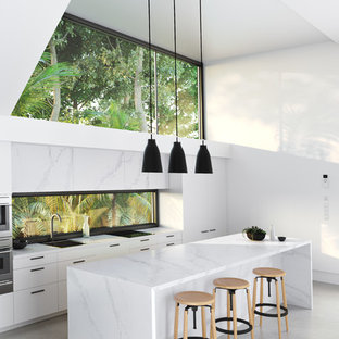 Offene, Zweizeilige Moderne Küche mit flächenbündigen Schrankfronten, weißen Schränken, Marmor-Arbeitsplatte, Rückwand-Fenster, Küchengeräten aus Edelstahl, Betonboden, Kücheninsel und grauem Boden in Sonstige