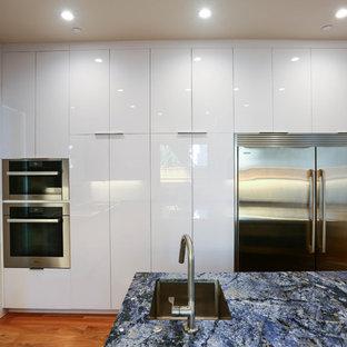 サンフランシスコの広いコンテンポラリースタイルのおしゃれなキッチン (シングルシンク、フラットパネル扉のキャビネット、黄色いキャビネット、御影石カウンター、白いキッチンパネル、ガラス板のキッチンパネル、シルバーの調理設備、無垢フローリング、青い床) の写真