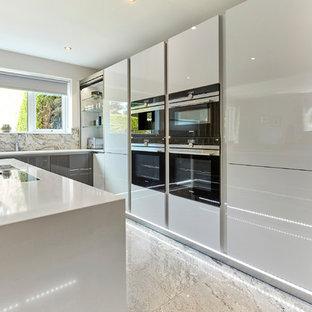 Idéer för att renovera ett mellanstort funkis vit vitt kök, med en integrerad diskho, släta luckor, vita skåp, bänkskiva i kvartsit, grått stänkskydd, stänkskydd i sten, svarta vitvaror, marmorgolv, en köksö och grått golv