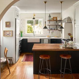 サンフランシスコの中くらいの地中海スタイルのおしゃれなキッチン (エプロンフロントシンク、落し込みパネル扉のキャビネット、白いキッチンパネル、磁器タイルのキッチンパネル、シルバーの調理設備、無垢フローリング、黒いキャビネット、大理石カウンター、茶色い床、白いキッチンカウンター) の写真