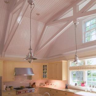 Idéer för att renovera ett stort vintage kök, med rostfria vitvaror, en rustik diskho, luckor med profilerade fronter, gula skåp, granitbänkskiva, stänkskydd i tunnelbanekakel och mellanmörkt trägolv