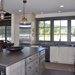 シアトルの広いラスティックスタイルのおしゃれなキッチン (アンダーカウンターシンク、シェーカースタイル扉のキャビネット、ヴィンテージ仕上げキャビネット、クオーツストーンカウンター、グレーのキッチンパネル、石タイルのキッチンパネル、シルバーの調理設備、無垢フローリング) の写真