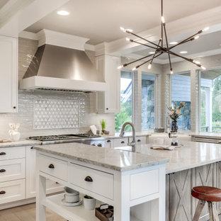 Klassisk inredning av ett stort vit vitt kök, med en rustik diskho, skåp i shakerstil, vita skåp, bänkskiva i kvarts, grått stänkskydd, stänkskydd i keramik, rostfria vitvaror, ljust trägolv, en köksö och grått golv