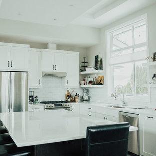 バンクーバーの中サイズのインダストリアルスタイルのおしゃれなキッチン (アンダーカウンターシンク、シェーカースタイル扉のキャビネット、白いキャビネット、珪岩カウンター、白いキッチンパネル、サブウェイタイルのキッチンパネル、シルバーの調理設備の、クッションフロア) の写真