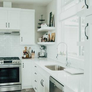 バンクーバーの中くらいのインダストリアルスタイルのおしゃれなキッチン (アンダーカウンターシンク、シェーカースタイル扉のキャビネット、白いキャビネット、珪岩カウンター、白いキッチンパネル、サブウェイタイルのキッチンパネル、シルバーの調理設備、クッションフロア) の写真