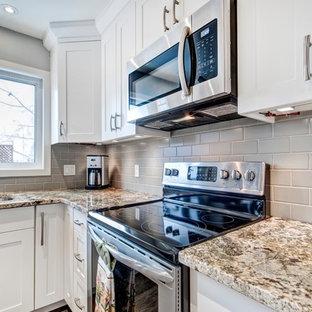 カルガリーの中サイズのトランジショナルスタイルのおしゃれなキッチン (アンダーカウンターシンク、シェーカースタイル扉のキャビネット、白いキャビネット、御影石カウンター、グレーのキッチンパネル、サブウェイタイルのキッチンパネル、シルバーの調理設備の、クッションフロア) の写真