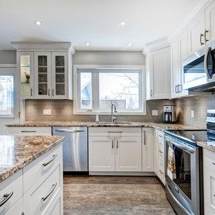 Mittelgroße Klassische Wohnküche in L-Form mit Unterbauwaschbecken, Schrankfronten im Shaker-Stil, weißen Schränken, Granit-Arbeitsplatte, Küchenrückwand in Grau, Rückwand aus Metrofliesen, Küchengeräten aus Edelstahl, Vinylboden und Kücheninsel in Calgary