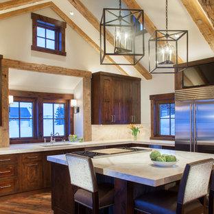 Inspiration pour une cuisine chalet en L avec un évier encastré, un placard à porte shaker, des portes de placard en bois sombre, une crédence en fenêtre, un électroménager en acier inoxydable, un sol en bois brun, un îlot central et un sol orange.