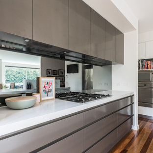 This is an example of a contemporary kitchen in Melbourne with flat-panel cabinets, grey cabinets, metallic splashback, mirror splashback, stainless steel appliances, dark hardwood floors, brown floor and white benchtop.