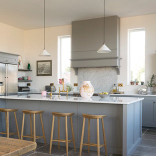 Photo of a large classic l-shaped open plan kitchen in Other with shaker cabinets, grey cabinets, quartz worktops, white splashback, marble splashback, stainless steel appliances, limestone flooring, an island and grey floors.