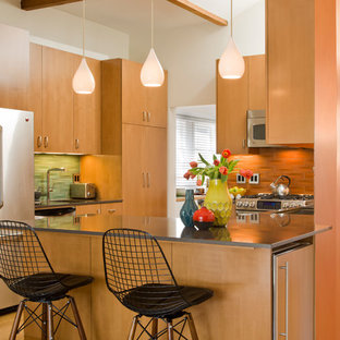 Inspiration for a mid-sized midcentury l-shaped open plan kitchen in Los Angeles with a drop-in sink, flat-panel cabinets, light wood cabinets, orange splashback, stainless steel appliances, light hardwood floors and no island.