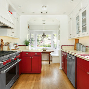 Traditional galley kitchen/diner in Los Angeles with a submerged sink, shaker cabinets, red cabinets, beige splashback, metro tiled splashback, stainless steel appliances, medium hardwood flooring, no island, beige floors and multicoloured worktops.