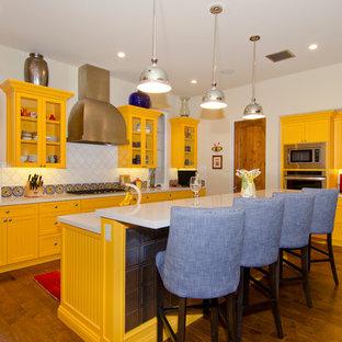 フェニックスの中サイズのサンタフェスタイルのおしゃれなキッチン (アンダーカウンターシンク、落し込みパネル扉のキャビネット、黄色いキャビネット、ライムストーンカウンター、白いキッチンパネル、シルバーの調理設備、無垢フローリング、セラミックタイルのキッチンパネル、茶色い床、白いキッチンカウンター) の写真