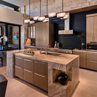 Inspiration for a large l-shaped kitchen/diner in Phoenix with a submerged sink, flat-panel cabinets, medium wood cabinets, limestone worktops, black splashback, stainless steel appliances, porcelain flooring, an island and beige floors.