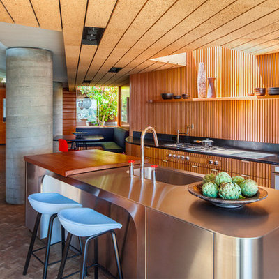 Inspiration for a 1950s brown floor eat-in kitchen remodel in Los Angeles with an integrated sink, medium tone wood cabinets, stainless steel countertops, brown backsplash, wood backsplash, paneled appliances and an island