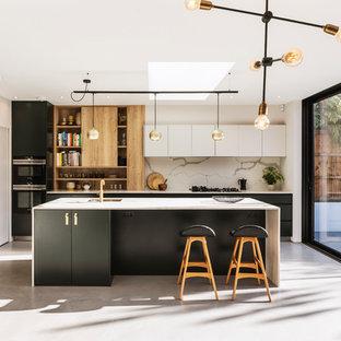 Nordische Küche mit Unterbauwaschbecken, flächenbündigen Schrankfronten, schwarzen Schränken, Küchenrückwand in Weiß, schwarzen Elektrogeräten, Betonboden, Kücheninsel, grauem Boden und weißer Arbeitsplatte in London