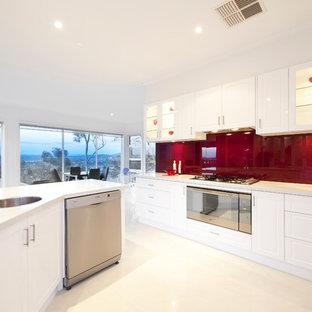 Idee per una cucina abitabile minimal con lavello da incasso, ante bianche, paraspruzzi rosso e elettrodomestici in acciaio inossidabile
