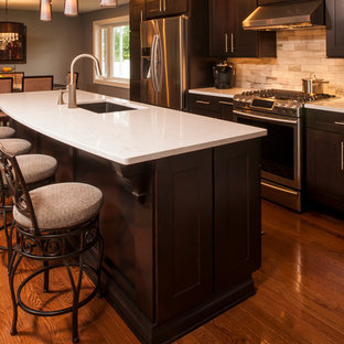 Mid-sized contemporary open concept kitchen photos - Inspiration for a mid-sized contemporary single-wall medium tone wood floor open concept kitchen remodel in New York with a single-bowl sink, recessed-panel cabinets, dark wood cabinets, quartz countertops, beige backsplash, stone tile backsplash, stainless steel appliances and an island