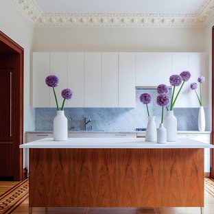 Design ideas for a medium sized modern galley kitchen/diner in Boston with a submerged sink, flat-panel cabinets, white cabinets, glass worktops, stainless steel appliances and an island.