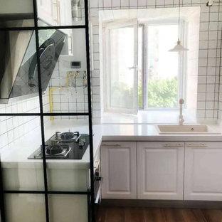 他の地域の小さいアジアンスタイルのおしゃれなキッチン (アンダーカウンターシンク、シェーカースタイル扉のキャビネット、白いキャビネット、クオーツストーンカウンター、白いキッチンパネル、セメントタイルのキッチンパネル、黒い調理設備、磁器タイルの床、アイランドなし、茶色い床、白いキッチンカウンター) の写真