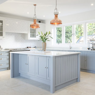 This is an example of a medium sized classic l-shaped kitchen in Sussex with shaker cabinets, white splashback, metro tiled splashback, stainless steel appliances, an island, blue cabinets and beige floors.