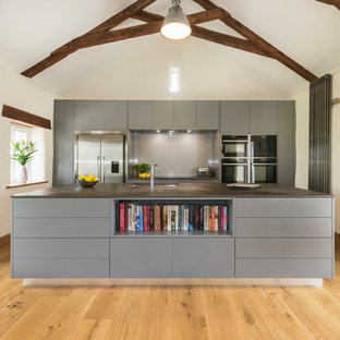 Inspiration for a medium sized contemporary single-wall kitchen in Cornwall with flat-panel cabinets, grey cabinets, grey splashback, stainless steel appliances, light hardwood flooring, an island, beige floors and black worktops.