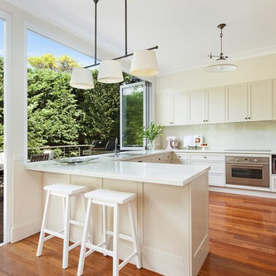Design ideas for a transitional u-shaped kitchen in Sydney with a drop-in sink, shaker cabinets, white cabinets, white splashback, glass sheet splashback, stainless steel appliances, medium hardwood floors, a peninsula, brown floor and white benchtop.